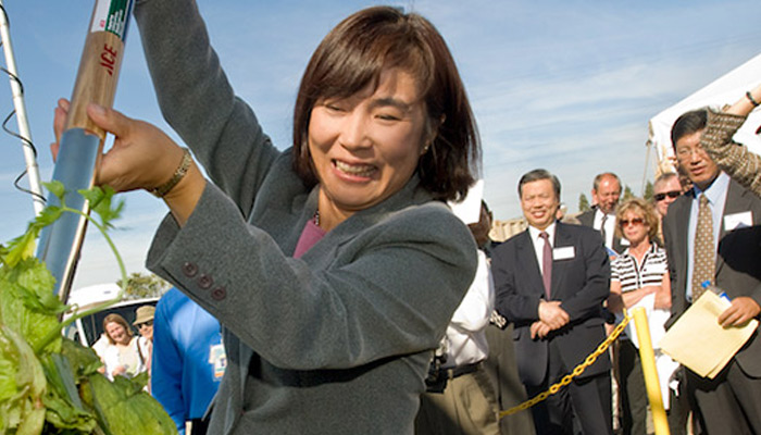 UC Davis Professor Ruihong Zhang shovels fresh table scraps biogas energy plant on the UC Davis campus. (Karin Higgins/UC Davis)