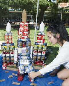 Student Jessica Truong makes adjustments to a castle of canned food that the Delta Epsilon Mu fraternity created in a fundraiser for The Pantry. (Jason Spyres/UC Davis photo)