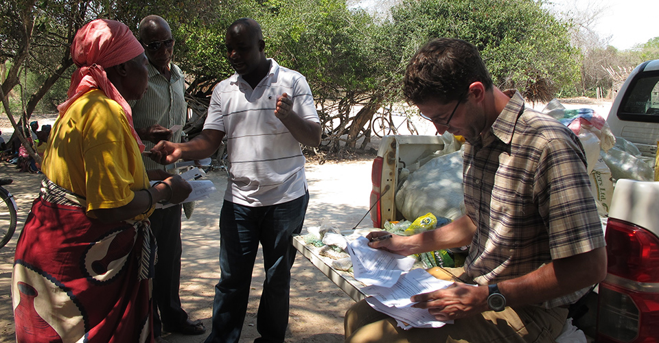 Jonathan Malacarne (right) reviews paperwork for seed and insurance purchases outside Chimoio in Mozambique. (AMA Innovation Lab)