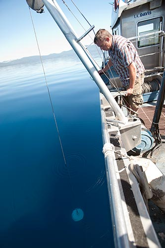 Research Associate Raph Townsend drops a Secchi disk and marks the depth when the disk disappears to check water clarity at Lake Tahoe, California. The UC Davis Tahoe Environmental Research Center does testing, monitoring, and conservation on the lake. (Photo credit: Gregory Urquiaga | UC Davis)