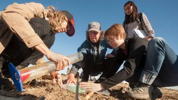 Professor Kate Scow (center, in hat) help students analyze infiltration rates in different soils at Russell Ranch Sustainable Agriculture Facility. (Gregory Urquiaga/UC Davis)