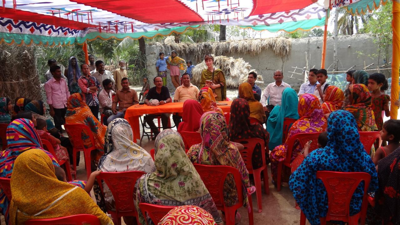 Hannah Waterhouse (standing middle center) introduces herself to a crowd of women gathered at a model farm to learn how to improve their homestead gardens in the Satkhira district of Bangladesh.