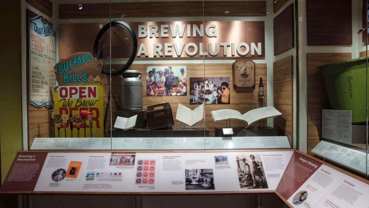 "New showcase in the National Museum of American History features UC Davis Professor Emeritus Michael Lewis on a placard, lower right, and his ""well-used and beat-up"" textbook in the display. (National Museum of American History)"