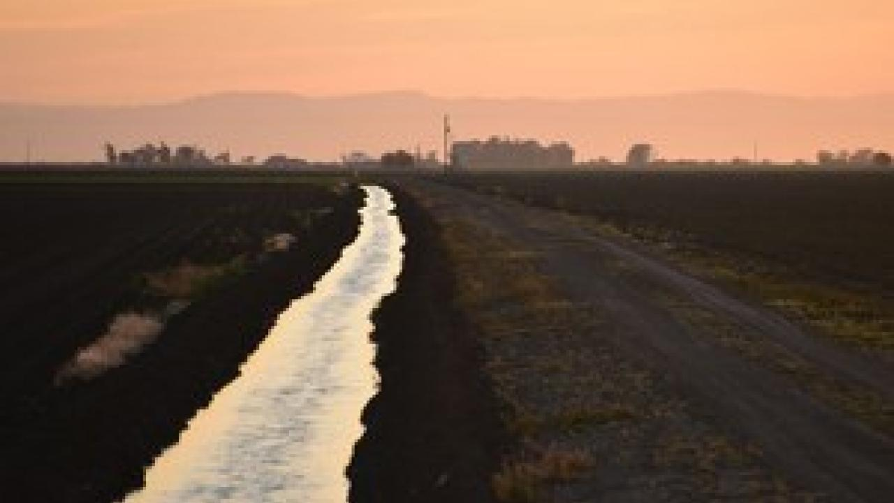 As the sun sets on this Merced County farm, water is conveyed in an unlined canal to more distant fields. State regulators increasingly are seeking to know how much water is being used throughout the state, and by whom. (Josh Viers | UC Merced)