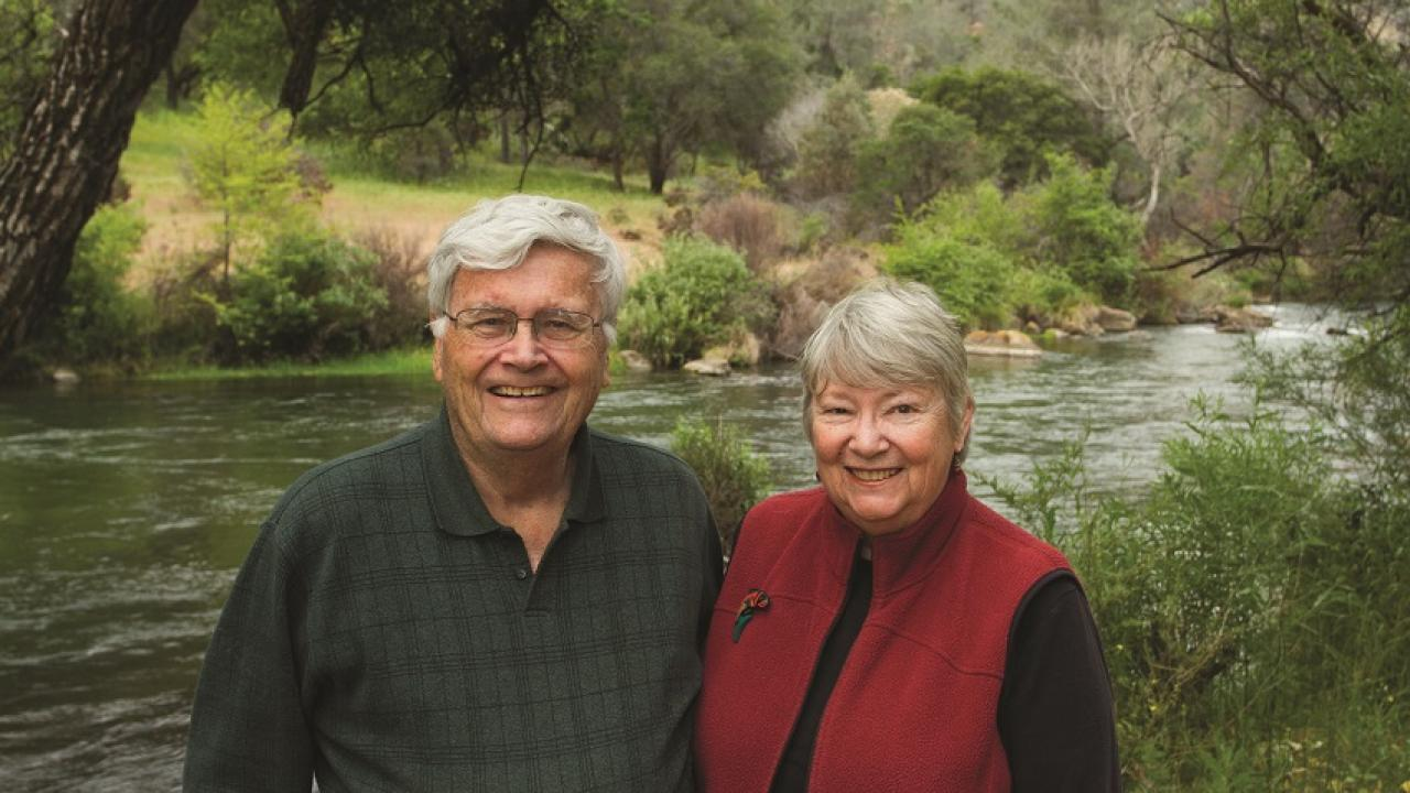 Tom and Ginny Cahill at Putah Creek and the land they donated to the university in the background.
