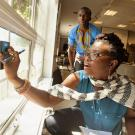 Ghislain Tandoh watches as Maame Tabuah Ankoh gauges window energy during an energy measurement class in the Mandela Washington Fellowship program. UC Davis will again host an energy institute for young African leaders this summer. (Gregory Urquiga/UC Davis)