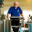 Bamforth standing by brewing equipment