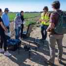 "Students learning to use a drone in the ""Introduction to Unmanned Aerial Systems for Agriculture and Environmental Science"" class last year."