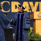 Helene Dillard shaking a newly graduated student's hand at the UC Davis CA&ES commencement.